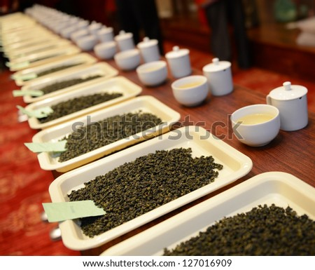 Group of fresh green tea leaves and tea in a row. - stock photo