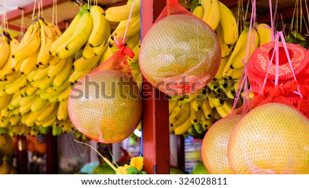 Group of fresh pomelo (Citrus maxima or Citrus grandis) fruits and bananas are hanging on display at the fruits stall at Bugis Village wet market, Singapore. Colorful urban concept. Soft focus - stock photo