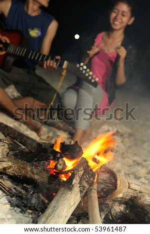 group of friend at beach with bonfire - stock photo