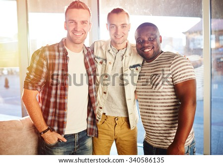 Group of friendly guys in casual-wear looking at camera - stock photo