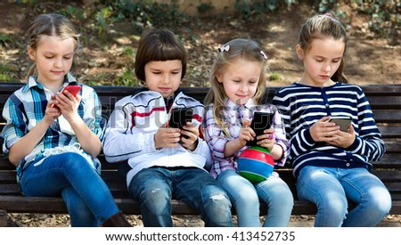 Group of friendly smiling children posing at urban street with mobile devices - stock photo