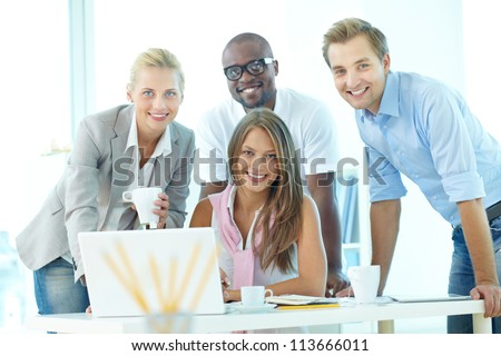 Group of friendly students or businesspeople gathered in front of laptop looking at camera - stock photo