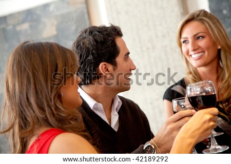 Group of friends at dinner in an elegant restaurant toasting - stock photo