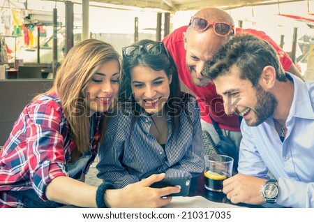 Group of friends at restaurant looking at phone - stock photo