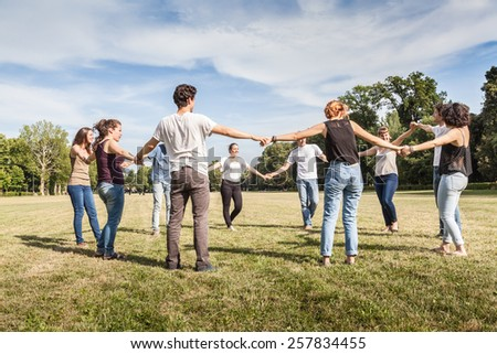 Group of friends at the park holding hands - stock photo
