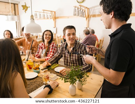 Group of friends at the restaurant and being served by the waiter - stock photo