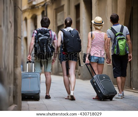 Group of friends at vacation walking at the street with luggage - stock photo