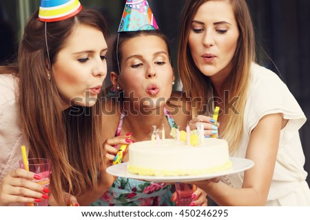 Group of friends blowing candles on birthday cake