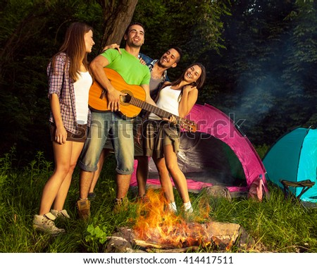 Group of friends camping.They are standing around a camp fire,singing and playing guitar. - stock photo