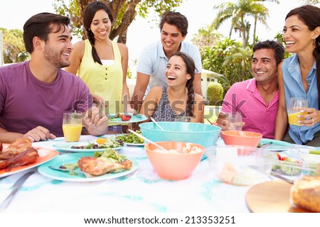 Group Of Friends Celebrating Enjoying Meal In Garden At Home - stock photo