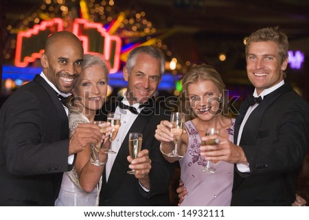 Group of friends celebrating win with champagne at casino