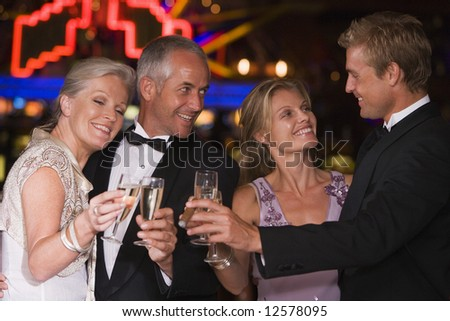 Group of friends celebrating with at casino with champagne