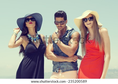group of friends chatting and having fun at the pool, three stylish friends standing by the pool  - stock photo