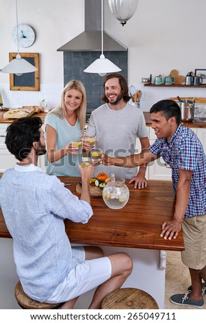 Group of friends cheers toasting in kitchen - stock photo