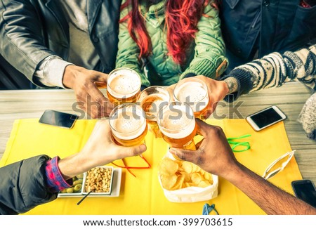 Group of friends cheers with beer cafe interior scene - Multiracial hands holding glasses of Pils in a toast to friendship and happiness -Teenager students gathering in restaurant -  Focus on glasses - stock photo