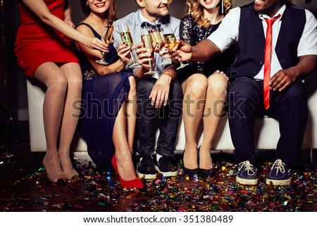 Group of friends clinking with champagne - stock photo