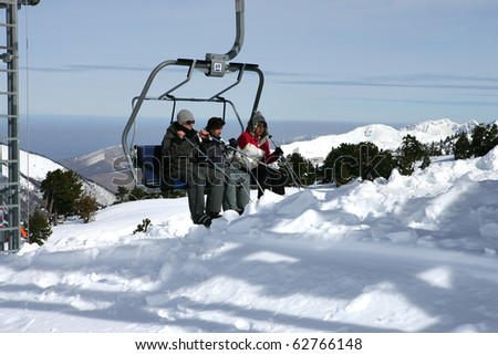 Group of friends coming down from a chairlift - stock photo