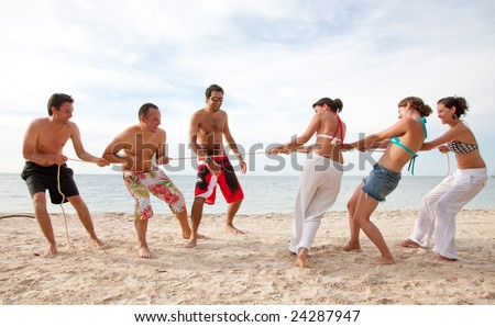 Group of friends competing pulling a rope at the beach - men against women - stock photo