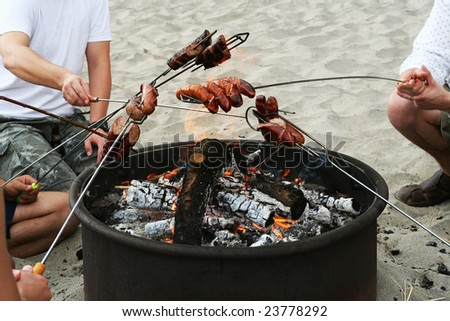 Group of friends cooking sausages on the fire on the beach - stock photo