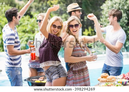 Group of friends dancing at outdoors barbecue party near pool - stock photo