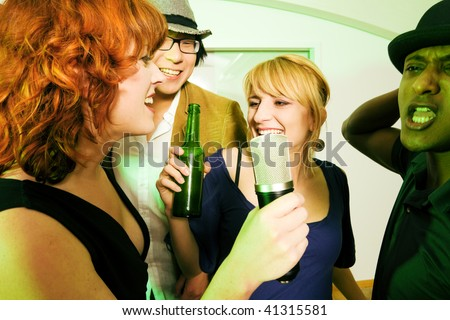 Group of friends (diversity) at a party in a club doing karaoke and drinking beer - stock photo