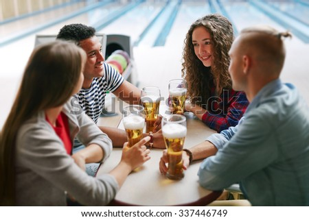 Group of friends drinking beer in bowling club - stock photo