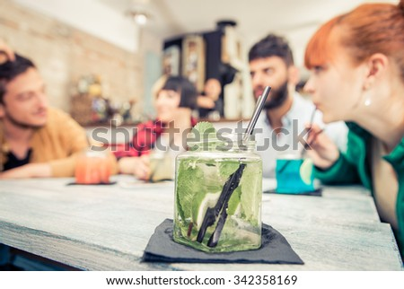 Group of friends drinking cocktail in a pub. Concept about friendship, drinks and service - stock photo