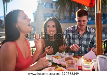 group of friends eating food together and laughing