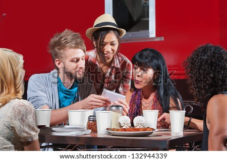 Group of friends eating out and looking at smartphone