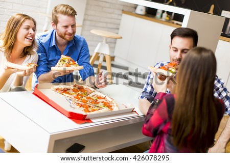 Group of friends eating pizza together at home