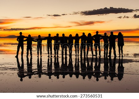 Group of friends embraced in the sunset light and wet salt surface in salares de uyuni, Bolivia. Orange sky with clouds background - stock photo
