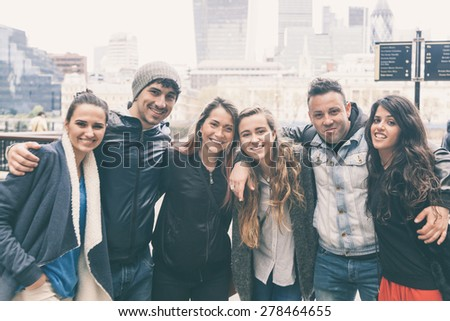 Group of friends embraced together in London. They are four girls and two boys in their twenties, friendship and lifestyle concepts, autumn clothing - stock photo