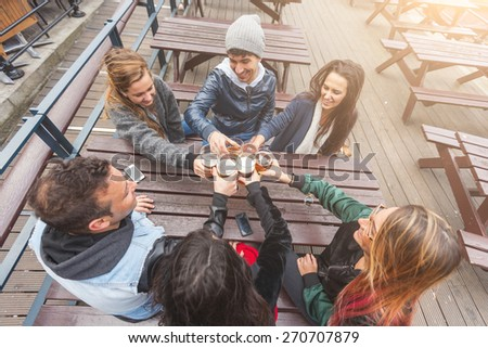 Group of friends enjoying a beer at pub in London, toasting and laughing. They are four girls and two boys in their twenties. - stock photo