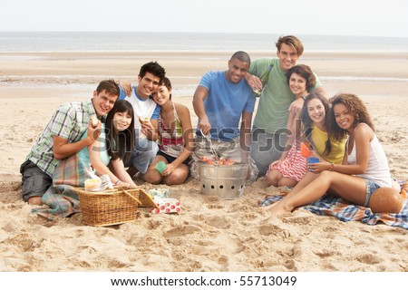 Group Of Friends Enjoying Barbeque On Beach Together - stock photo