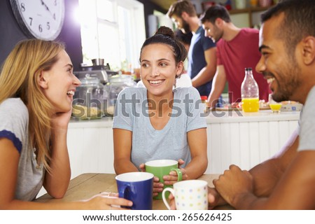 Group Of Friends Enjoying Breakfast In Kitchen Together - stock photo