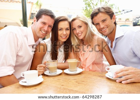 Group Of Friends Enjoying Coffee In Cafe - stock photo