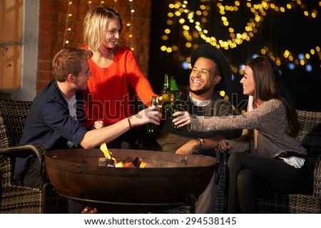 Group Of Friends Enjoying Evening Drinks By Firepit - stock photo