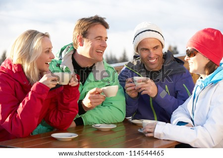 Group Of Friends Enjoying Hot Drink In Cafe At Ski Resort