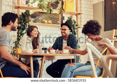 Group of friends enjoying in cafe together. Young people meeting in a cafe. Young men and women sitting at cafe table and smiling - stock photo