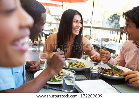 Group Of Friends Enjoying Meal At Outdoor Restaurant - stock photo