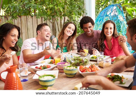 Group Of Friends Enjoying Meal Outdoors At Home - stock photo