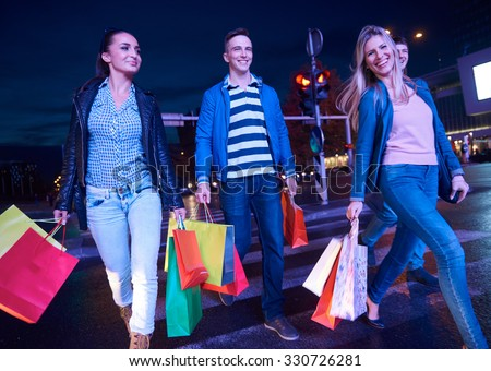 Group Of Friends Enjoying Shopping Trip Togethergroup of happy young frineds enjoying shopping night and walking on steet on night in with mall in background - stock photo