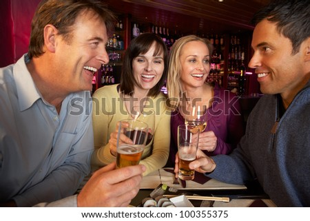 Group Of Friends Enjoying Sushi In Restaurant - stock photo