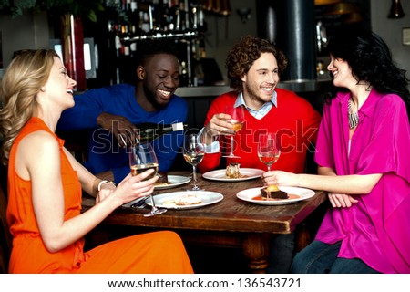 Group of friends enjoying their dinner with drinks at a restaurant. - stock photo
