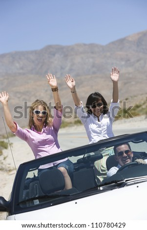 Group of friends enjoying their journey in car - stock photo