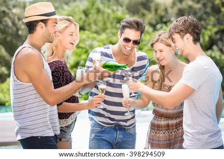 Group of friends enjoying while having champagne near pool - stock photo