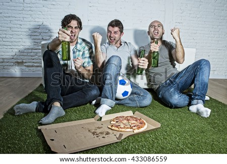 group of friends fanatic football fans watching soccer game on television celebrating goal on grass carpet emulating stadium pitch screaming excited and ecstatic crazy happy with beer and pizza - stock photo