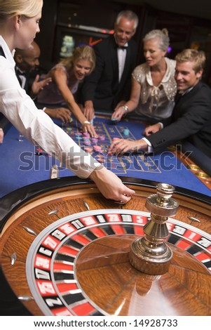 Group of friends gambling at roulette table - stock photo