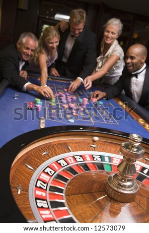 Group of friends gambling at roulette table in casino - stock photo