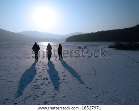 group of friends going ahead on the frozen lake to the sun - stock photo